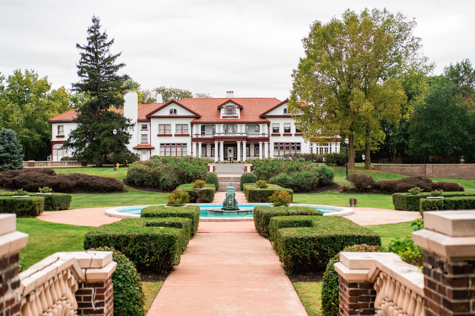 wide-angle exterior of completed longview mansion development project with fountain and bushes