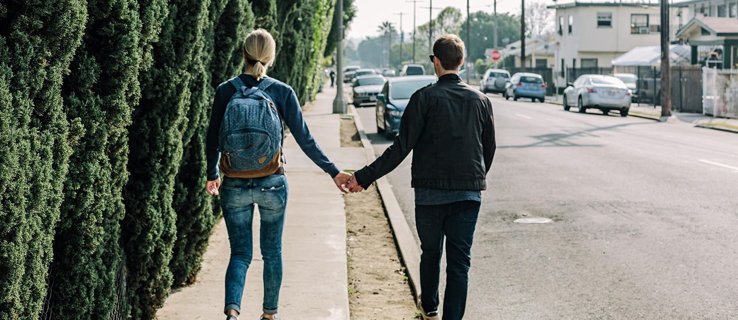 Couple holding hands as they walk on the side walk in an up-and-coming neighborhood.